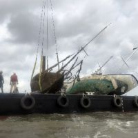 Sunken vessel being lifted from the water onto a boat.