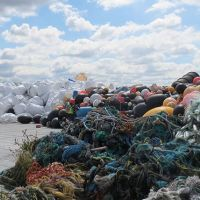 Old fishing nets and bagged debris on a beach.