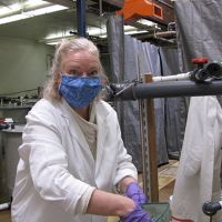 Woman in a mask and white coat working at a tank.