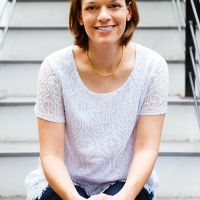 A woman posing for photo while sitting on stairs.