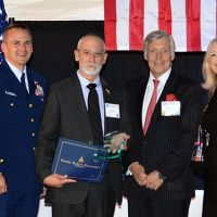 Four people posing for photo with an award in front of a flag.