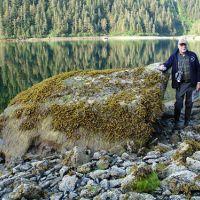 Man standing next to large boulder.