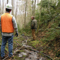 Two men standing in a wooded area.