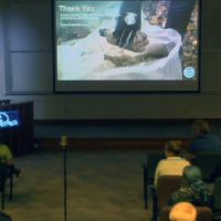 People in a dark classroom look at a presentation on a large screen