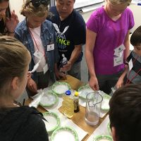 Man demonstrating an experiment to young students gathered around a table.