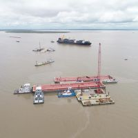 An aerial view of three barges with several vessels around them.