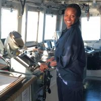 Woman standing in the wheelhouse of a vessel.