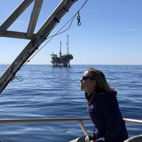 Woman in a boat with oil well in background.