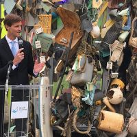 Man speaking against a backdrop of a display of trash.