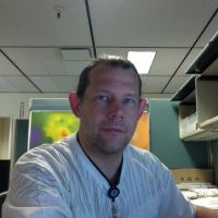Headshot of a man at a desk.