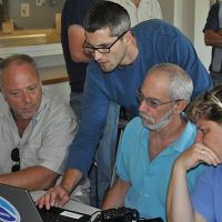 Four people looking at a computer.