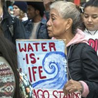 Woman demonstrating with sign.
