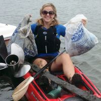 Woman on a boat with bags of debris.