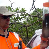 Man holding a sample in a clear container.