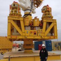 Woman in front of large piece of industrial equipment.