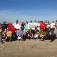 Group posing on a beach.