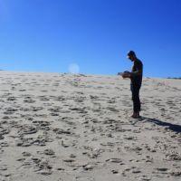 Man standing alone on a beach.