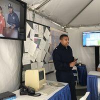Man speaking from corner of exhibit tent.