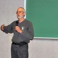 Man in front of blackboard speaking into microphone.