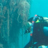 Diver underwater with huge tangle of nets.