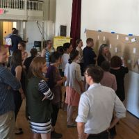 Group of people doing an exercise at a bulletin board.