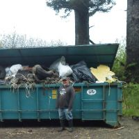 Man stands in front of full dumpster.