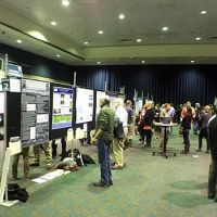 People standing in large hall looking at posters.