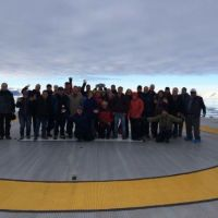 Group of people standing on a helicopter pad.