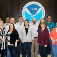 Group of people in front of a NOAA logo.
