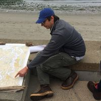 Man looking at nautical chart on a beach.