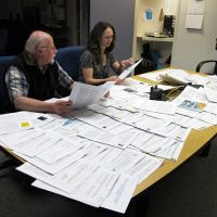 A man and a woman at a table with lots of papers spread out.