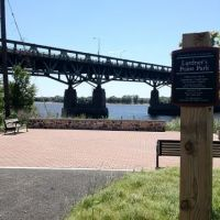 Park entrance sign in foreground, with bridge in background.