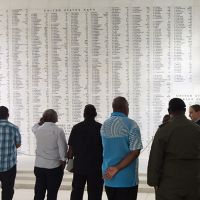 Group stands looking at a wall of names.