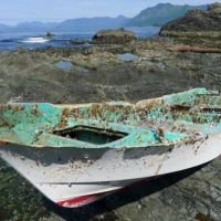 Boat covered in barnacles on a rocky beach.