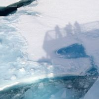 Shadow of crew members reflected on Arctic Ice.