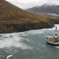 A drilling rig floating near an island.