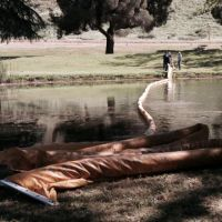 Shallow water containment boom stretched across a stream in California.