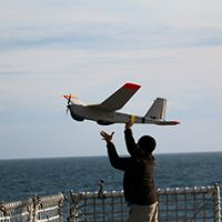 Man launches a large remote-controlled plane by hand from a ship deck.