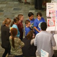 A group of students present on marine debris in front of a stand-up poster.