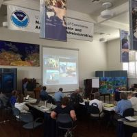 People in a conference room listen to and watch a presentation on spill response