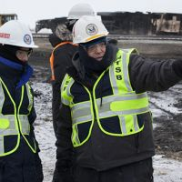 Officials standing next to a burned-out, derailed train.