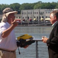 Two men with a small underwater sensor in hand talking on a pier.