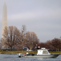 A boat on water with a monument on the shoreline in the background.