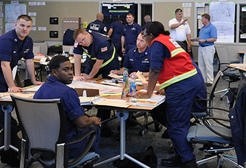 Coast Guard staff standing at tables during a training in the Disaster Response Center.