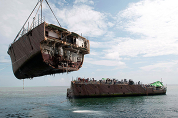 A crane vessel removes the bow of the mine countermeasure ship Ex-Guardian.