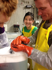 Three people help wash an oiled goose in big soapy wash tubs.