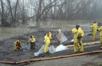 Workers collect oiled debris following an oil spill on a river.