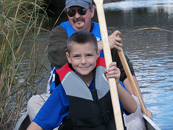 A man and his grandson canoeing on Woodbridge River.
